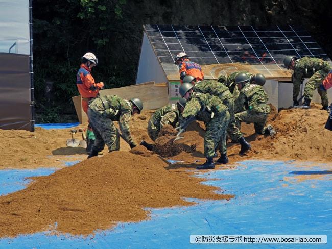 陸上自衛隊第3特科隊がバケツリレー方式で、埋もれた家屋の土砂を素早く排出。