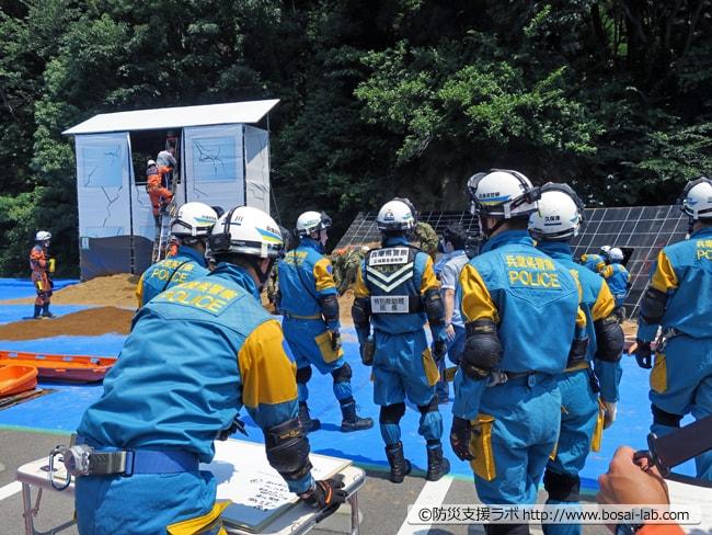 兵庫県警の現場指揮所からの視点。左側の家屋では神戸市の消防士が自力歩行可能な要救助者を支えながら救助が進む。