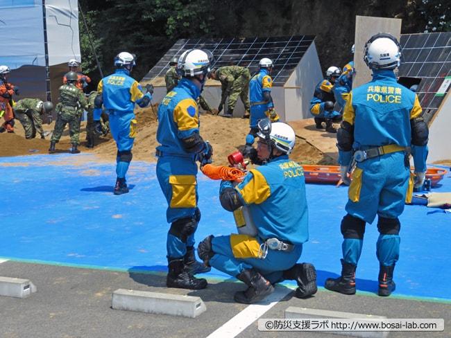 多彩なエアー工具のうちエアーソーを準備する兵庫県警。空気呼吸器の高圧空気ボンベで稼働するため、工具自体はコンパクト。