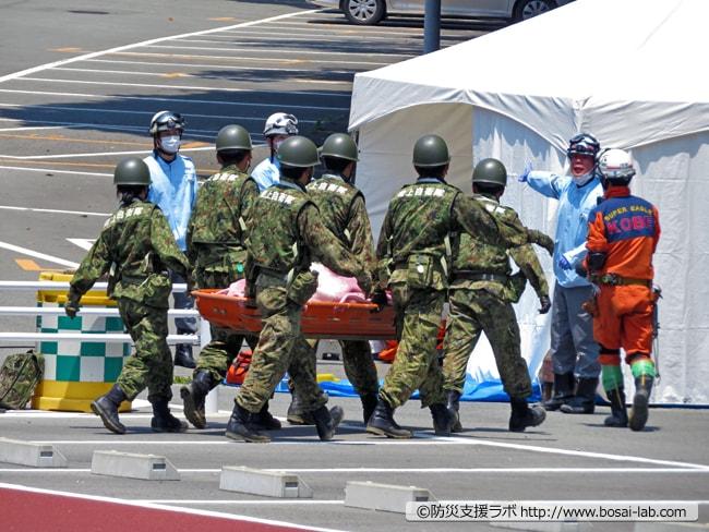 消防士が先導しつつ陸上自衛隊が要救助者を設営された本部の救護所まで搬送へ。