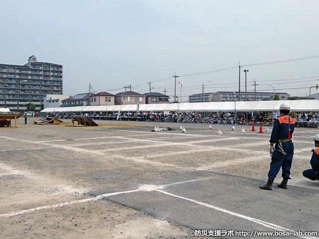 防災訓練前の会場の様子。会場自体は市街地にあり、白いテントにて避難訓練に参加する多数の住民の姿も見る事が出来る。