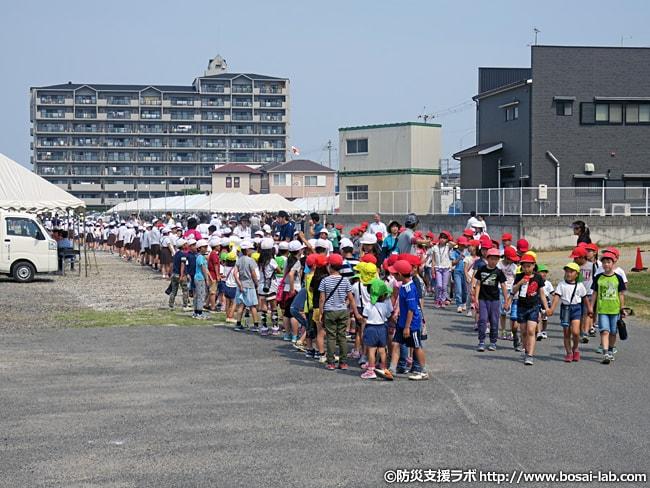 集団避難訓練の列は幼稚園児を真ん中にして、その両脇に小学生が見守る形で進行。バックパックなど持ち出し袋は背負っている様子は無かったが、帽子と水筒を所持した状態で参加。