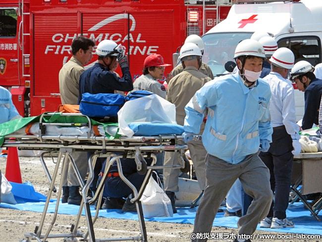 岸和田市消防本部の感染防止衣を着用した救急救命士が救急資器材をストレッチャーに乗せて駆けつける様子。