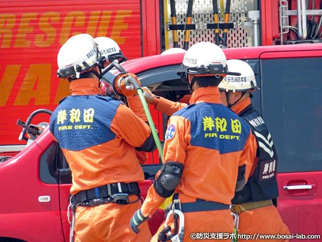岸和田市消防本部のレスキュー隊(特別救助隊)による車輌に閉じ込められた市民の救助訓練を展開。大型救助器具である油圧式のスプレッダー(ウエッジ)を差し込んで、ドアの解放を試みています。また、岸和田市のレスキュー隊のユニフォームは他の地域と違って特徴的な字体を採用。
