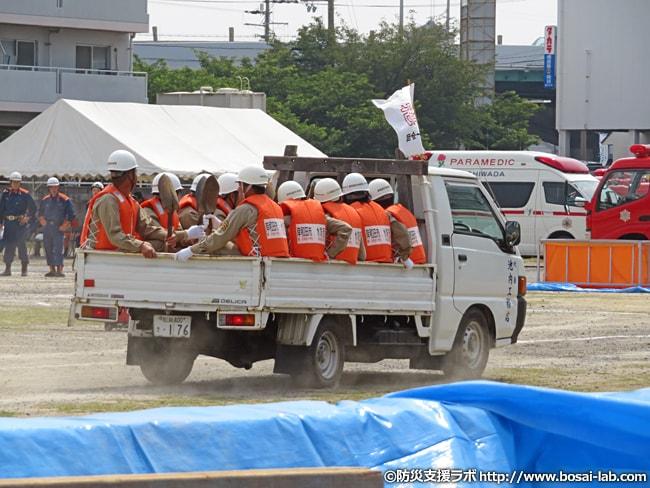 岸和田市の多数の水防団員がトラックの荷台へ10人ずつ乗り込んで訓練会場へ入場。