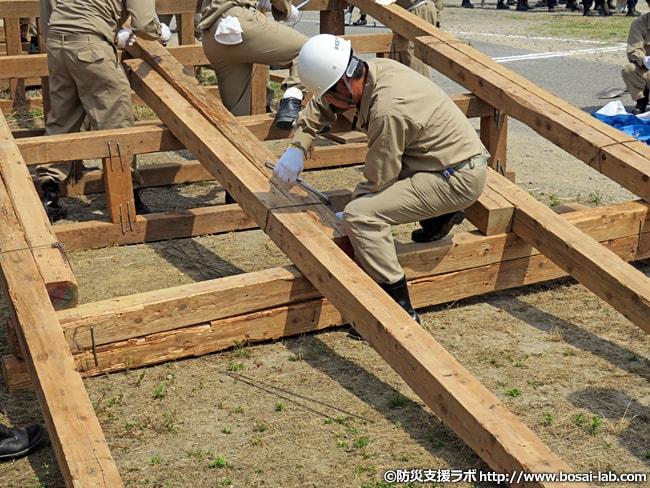 水防団が仮設橋を組み上げ中。他の団員と協力して番線(鉄製の太い針金)で固定中。
