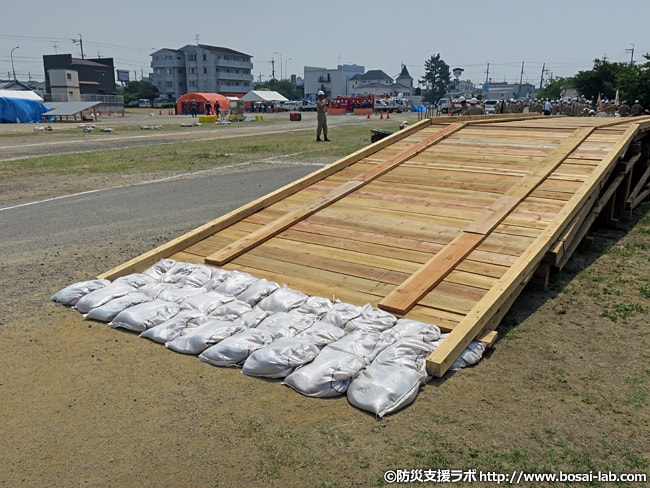岸和田市の水防団による仮設橋が完成。進入口と退出口には土のうが設置されています。