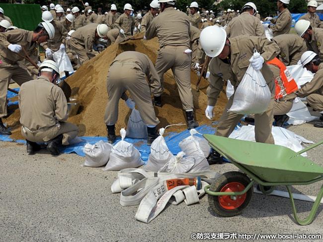 水防団による土のう作成状況。多数の水防団員が参加しており、大量の土のうがどんどん運ばれていきます。
