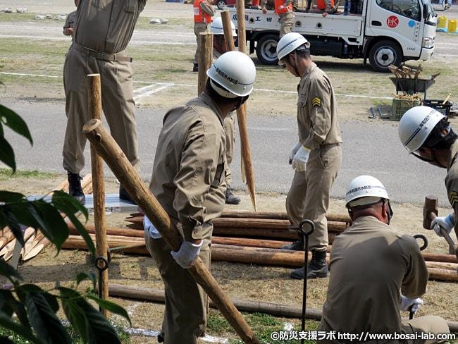各水防工法の設置を始める水防団員の方々。木製や金属製のくいを大ハンマーで差し込んでいき、柵へと連結してきます。