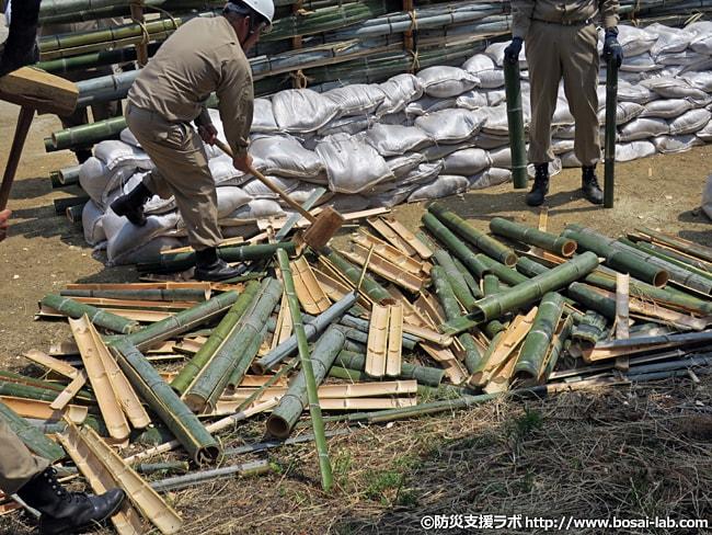 水防工法の一つ、築廻し工のパーツを作成している様子。柵に用いる竹に切り込みを入れて木槌で一気に割り、竹の節も取り除きます。