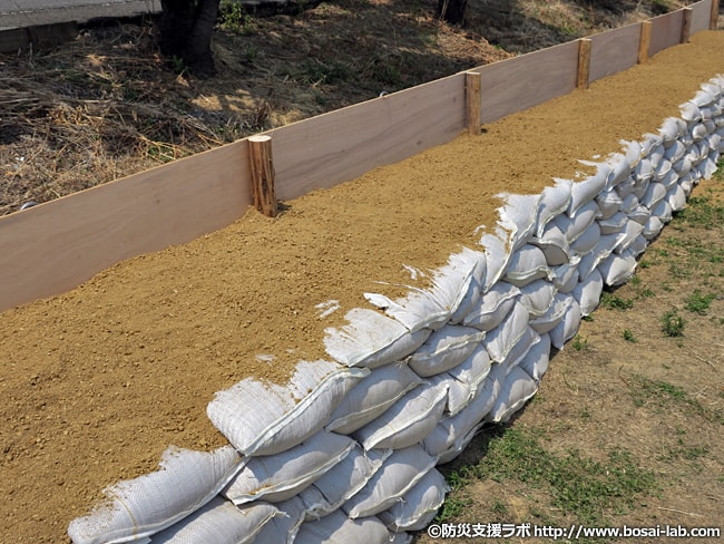 水防団による各水防工法が完了。木製の柵に土のうを5段積んだもの。堤防からの水のあふれ(越水)の対策に用いられる。