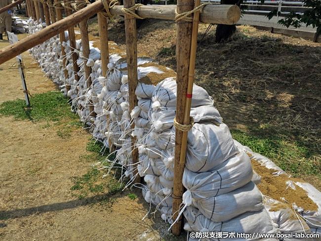 水防団による長い木製のくい打ちと土のう積みを組み合わせた工法。堤防の斜面崩れに対応。