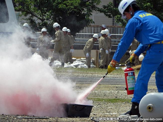 消火器を用いた初期消火の訓練。実際に火を着けた状態で実施され、水消火器でなく粉末消火器で対応、なるべく実際の対応に近い手順で進められていました。