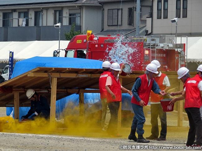 初期消火の訓練の別エリアでは、巨大水槽から防火用バケツで汲み、住民参加によるバケツリレーを実施。