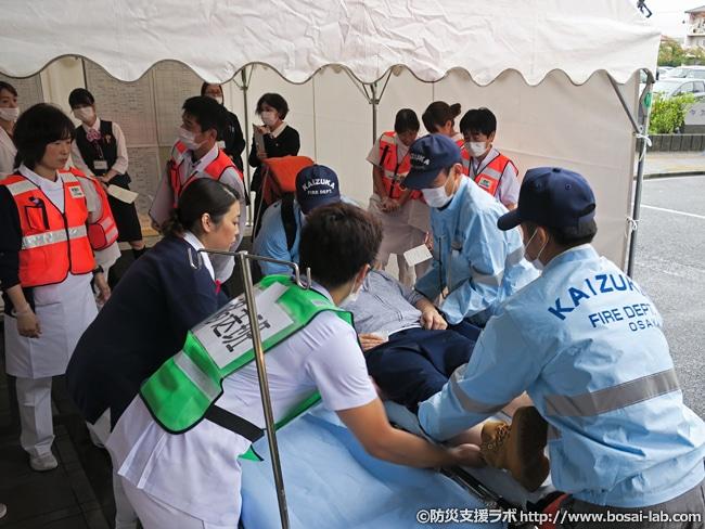 トリアージポスト前にて、救急搬送された傷病者を院内移送用のストレッチャーへと移し替え。