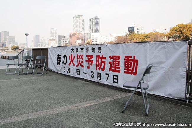 平成30年春の火災予防運動オープニングイベントの垂れ幕。オープニングイベント自体は2月25日、大阪の天満橋駅前、る八軒家浜船着場付近で行われました。