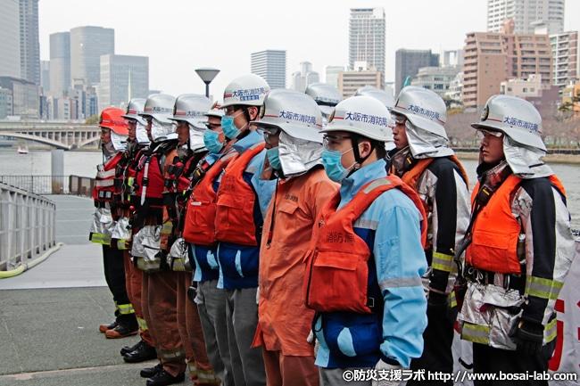 1日消防署長、西川忠志さんへの船舶火災総合訓練終了報告。