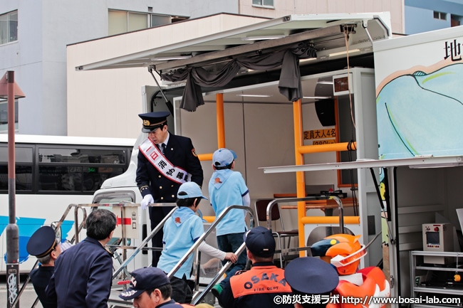 地震体験エリアでお子様と共に乗り込む西川忠志さん。